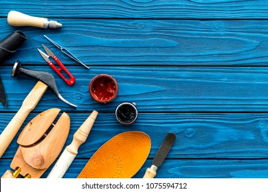Instruments and materials for make shoes. Shoemaker's work desk. Hummer, awl, knife, sciccors, wooden shoe, insole, paint and leather. Blue wooden background top view copy space
