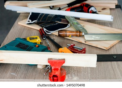 instruments on table for carpentry.saw,small piece of wood,electric screwdriver,spirit level,plank,wood,measurement,level tools,tape measure,plank wood,sawing the wood, C-clamp,G-clamp,woodwork.