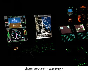 Instruments panel of a helicopter cockpit flying over the airfield or airport at night. Interior of helicopter control dashboard at night with glass cockpit or fly-by-wire system. mfd, pfd and mcdu.