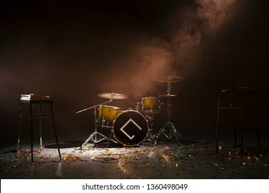 Instruments of a rock band in a concert hall. The floor of the room is confetti.