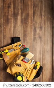 instruments in tool belt at wooden table surface background