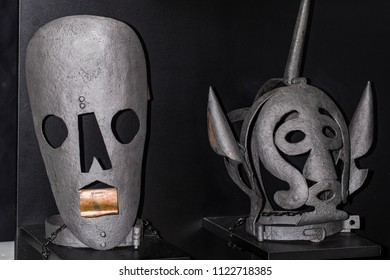 Instruments of torture times of inquisition two gray masks on a black background