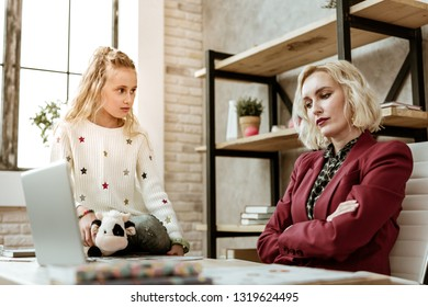 Insufferable gesture. Frustrated unpleasant mother sitting with crossed hands while offended daughter looking on her