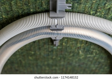 Insulated back of a dishwasher with two rolled-up water hoses.