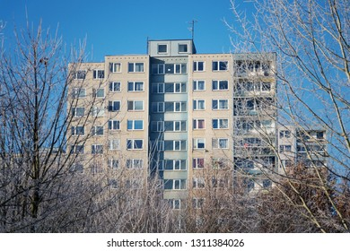 Insulated panel house apartments behind trees, high-rise block of flats, prefabricated tower blocks from concrete slabs, large panel system building, energy effeciendy building concept, winter day