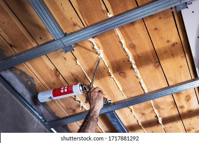 Insulation of boards on the ceiling using mounting foam. Ceiling thermal insulation close-up