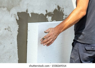 Insulation of facade wall with styrofoam sheets. Polystyrene insulation boards with glue adhesive.