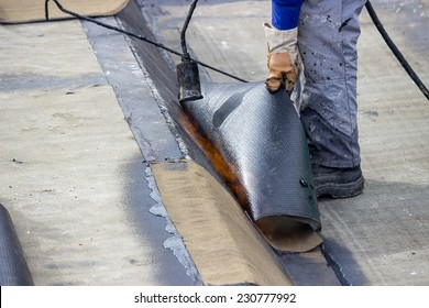 Insulation worker with propane blowtorch at floor slab insulation work. Worker heating and melting bitumen felt.