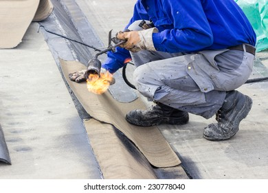 Insulation worker with propane blowtorch at floor slab waterproofing works. Worker heating and melting bitumen felt. Water proofing of concrete structure.