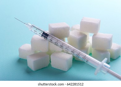 Insulin syringe from diabetes along with sugar cubes. Empty place for text copy paste