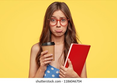 Insulted pupil purses lips with offense, drinks takeaway coffee being in bad mood after failing exam, wears glasses, uses scientific literature, isolated over yellow background. Education concept