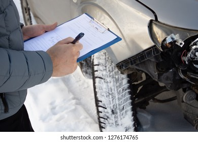 Insurance agent checking car after car accident and filling accident details form. Winter time. Focus on hands.