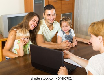 Insurance agent consulting happy young family with kids at home. Focus on woman