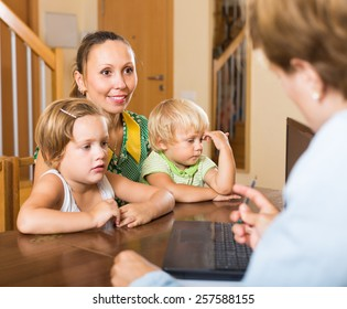 Insurance agent consulting smiling woman with two little children at home