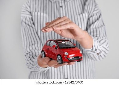 Insurance agent covering toy car on grey background, closeup