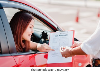 Insurance agent hand over car insurance document to asian woman client in car