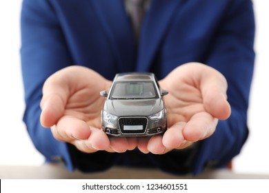 Insurance agent holding toy car over table, focus on hands