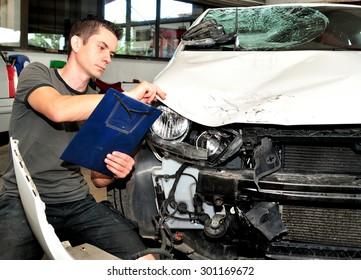 Insurance agent inspecting car damage.