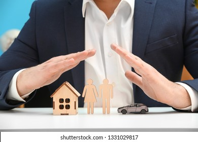 Insurance agent with toy car, human figures and house sitting at table, closeup