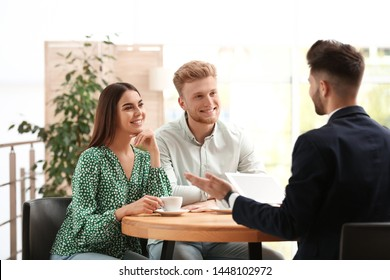 Insurance agent working with young couple in office