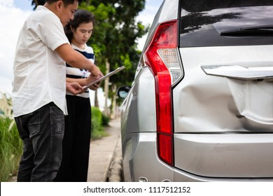 Insurance agent writing on clipboard while examining the car after accident claim was assessed and processed,traffic accident and insurance concept