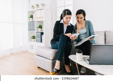 insurance agent and the young girl discussing the insurance plan and counting on calculator. bright home office lifestyle. Female agent consulting clients in living room.