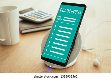 Insurance claim concept. The mobile smartphone is placed on a wireless fast charger on the screen with an insurance claim form.