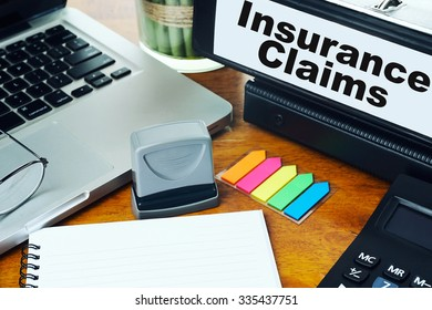 Insurance Claims- Ring Binder on Office Desktop with Office Supplies. Business Concept on Toned and Blurred Background