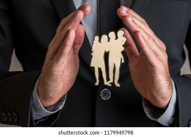 Insurance concept with businessman holding protective or healing hands gesture around a silhouette of a family cut out of paper.