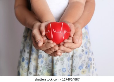 Insurance concept. Happy family holding red heart in hands on light background, closeup