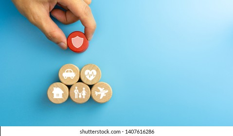 Insurance concept. Wooden blocks with insurance icons. family, life, car, travel, health and house insurance icons. blue background with copy space