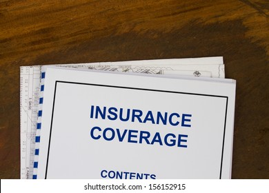 insurance coverage abstract with blueprints and coffee.