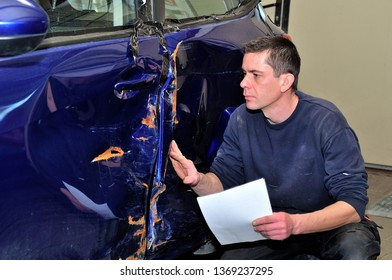 Insurance expert working at damaged car.