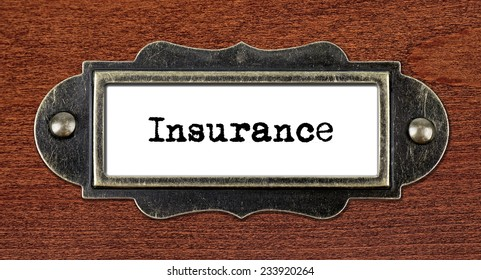 Insurance - file cabinet label, bronze holder against grunge and scratched wood