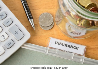Insurance file with calculator, pen, coins and glass jar