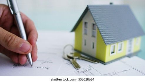 insurance of fire and theft .the hands of an insurer or real estate agent showing a house with floor plan and documents with ensured house keys.concept of home protection, family, insurance.rent house