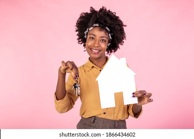 Insurance, loan, real estate and family concept. Surprised and amazed black female holding paper house and house keys, searching perfect home, pink background