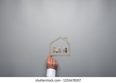 Insurance and safety concept - family made of pebbles in paper frame of a house over grey background.