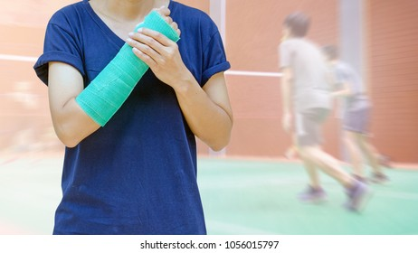 insurance sport, badminton player with green cast on arm on blurred badminton courts with players competing.