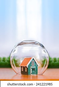 Insured house concept. Toy house protected in glass sphere with copy space above