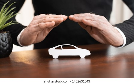 Insurer protecting a car with his hands