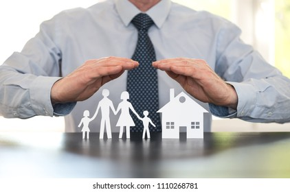 Insurer protecting a family and a house with his hands