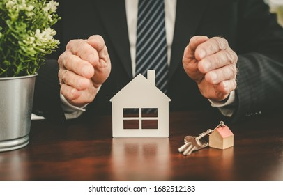 Insurer protecting a house with his hands