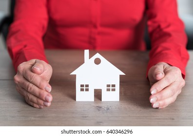 Insurer protecting house with his hands