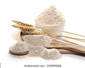 Integral barley flour and wheat ears with wooden spoon and bowl isolated on white background