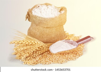 Integral barley flour and wheat ears with wooden spoon and bowl isolated on white background          - Image