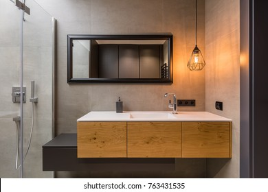 Integral countertop sink on wooden cabinets in contemporary bathroom