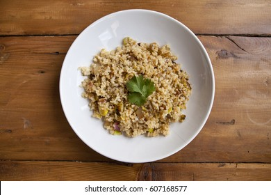 integral rice with vegetables dish in a wooden background with crackers and lemonade