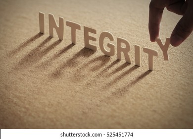 INTEGRITY wood word on compressed board with human's finger at Y letter