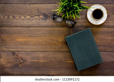 Intellectual entertainment concept. Books with empty cover near glasses, coffe, plant on dark wooden desk top view copy space